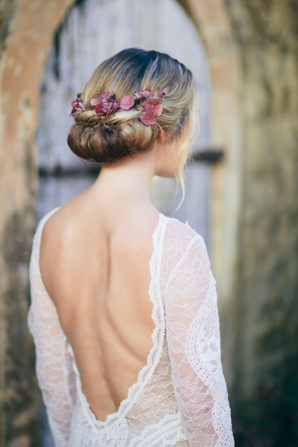 wedding updos-loose roll looks ultra-romantic with the addition of face-framing waves and pink blooms tucked in back
