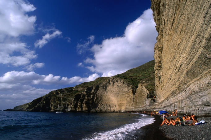 Narrow and dwarfed by the cliff behind stretches the well attended pebble beach of Pollara, Salina island.