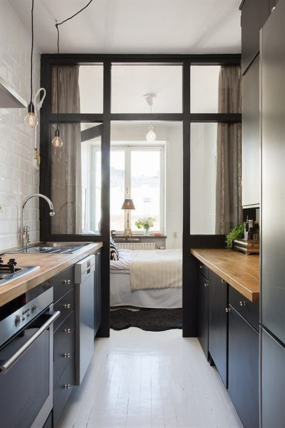 The ceiling height window wall in this galley kitchen makes small space seem airier, while curtains provide privacy in the bedroom.  I love the Edison lamps for a little bit of flair.
