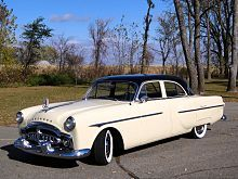 """The 1951 Packards were at last completely redesigned. Designer John Reinhart introduced a high, more squared-off profile that was sleek and contemporary and looked as far from the bathtub design of 1948/50 as one could get. New styling features included a one-piece windshield, a wrap-around rear window, small tailfins on the long-wheelbase models, a full-width grill, and """"guideline fenders"""" with the hood and front fenders at the same height."""