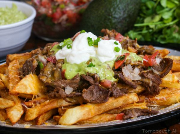 Carne Asada Fries - Delicious Carne Asada atop a heaping pile of french fries loaded with cheese, sour cream and guac!