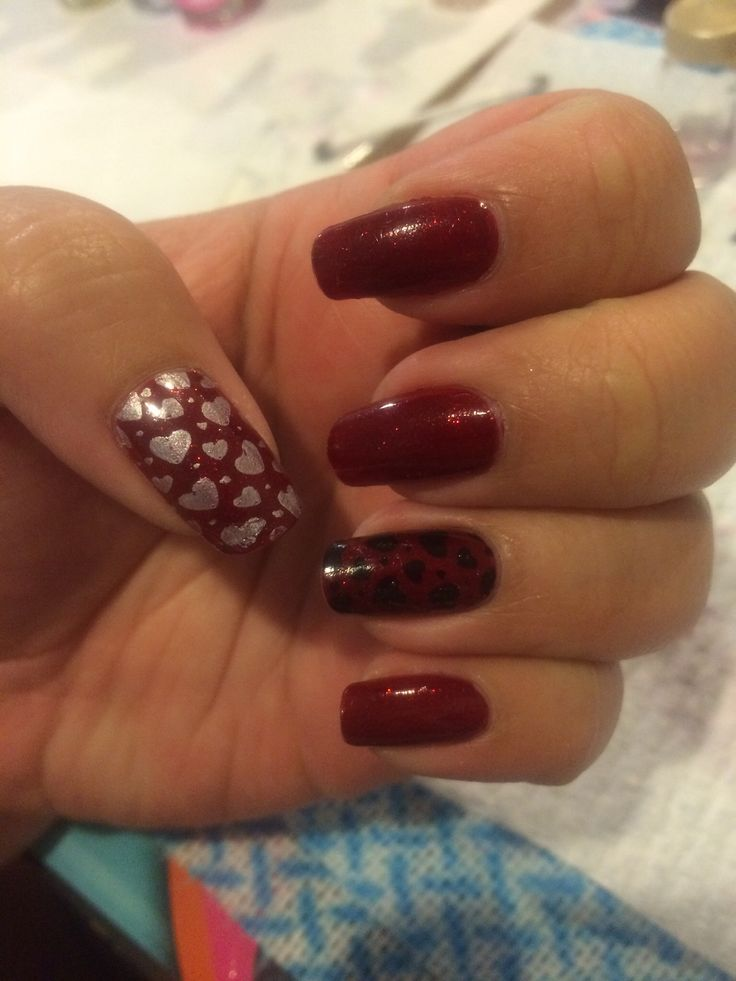 Nail design. Red sparkly base with silver and black heart stamping.