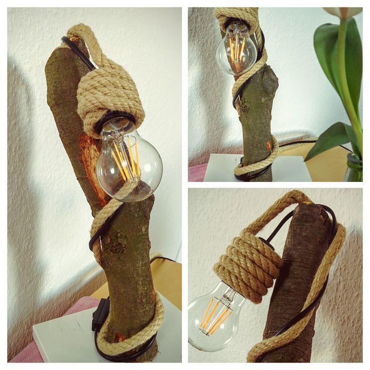 Lampe aus Holz - Material: Holzstamm/dicker Ast (aus dem Wald, vom Feuerholz, o.ä.), Brett + weißer Holzlack zum lackieren, schwarze Fassung und schwarzes Kabel mit Schalter aus dem Baumarkt, Tau/Seil aus dem Baumarkt, LED-Lampe, Schrauben, einmal für die Verbindung vom Ast mit dem Brett und einmal zum Fixieren des Seils oben auf dem Ast, Heißkleber, um das Seil an 2-3 Stellen am Ast zu fixieren (Das Kabel wurde ohne weitere Fixierung nur um das Tau/Seil gelegt.)