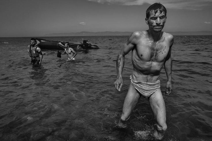 A migrant walks towards shore in Lesbos, Greece after swimming from the inflatable boat he had taken in the crossing from Turkey, Sept. 27, 2015.  James Nachtwey: The Journey of Hope