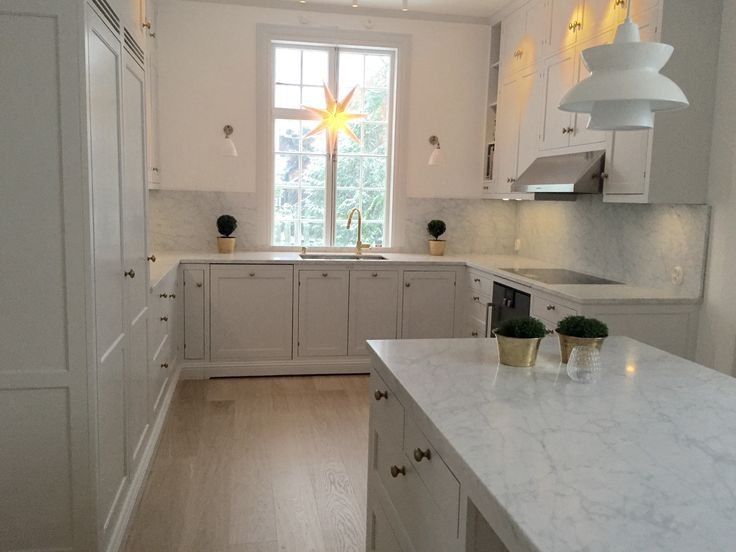 Light grey kitchen with Carrara marble countertops and kitchen island