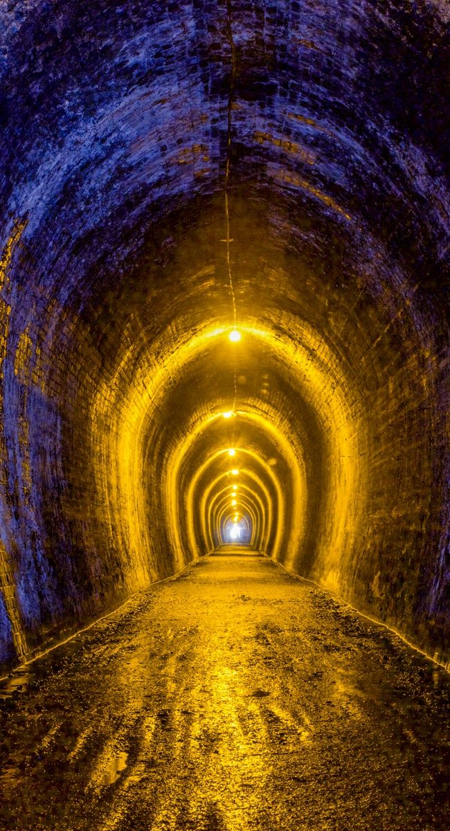 Here's the 1km long tunnel on the Karangahake Gorge Walkway, New Zealand. This used to be a railway tunnel in gold mining times.