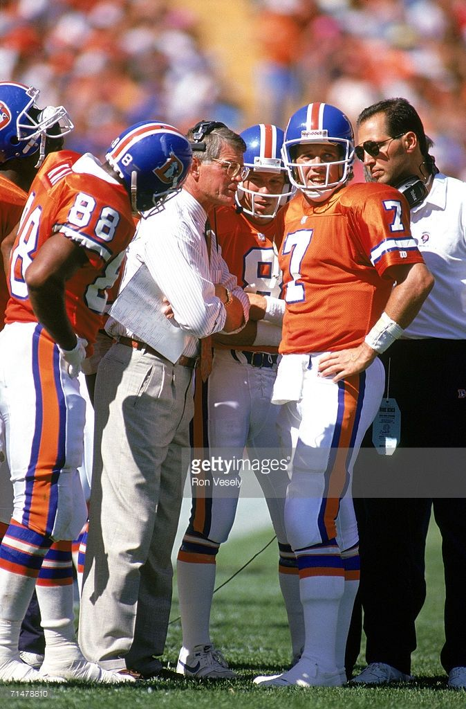 Head coach Dan Reeves and quarterback John Elway #7 of the Denver Broncos stand on the sideline during a circa 1980s game at Mile High Stadium in Denver, Colorado.
