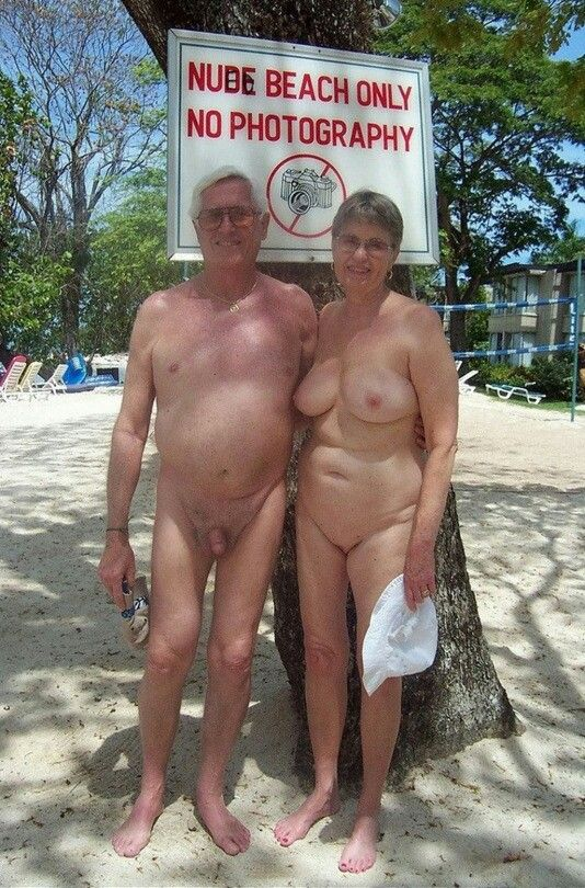 Naturists couples enjoy there sunbath in the nude beach 4