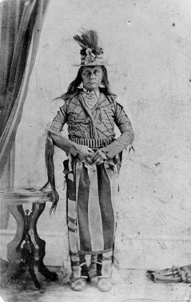 Studio portrait of Cayuse Indian, wearing beaded jacket, decorated straw hat, jewelry and munitions belt. Identified as Cutmouth John, who acted as a scout after the Whitman massacre .  ca 1865