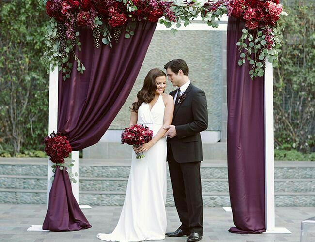 Wedding arch decoration   ceremony backdrop   deep wine asymmetrical draping embellished with vibrant florals