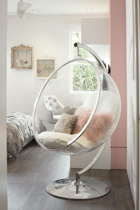 A cosmic chair forms a focal point in this bright and airy girl's bedroom. Glamour, sparkle and romance combine in the accessories, while white walls keep the backdrop crisp and clean. A blush pink accent wall adds a delicate touch.