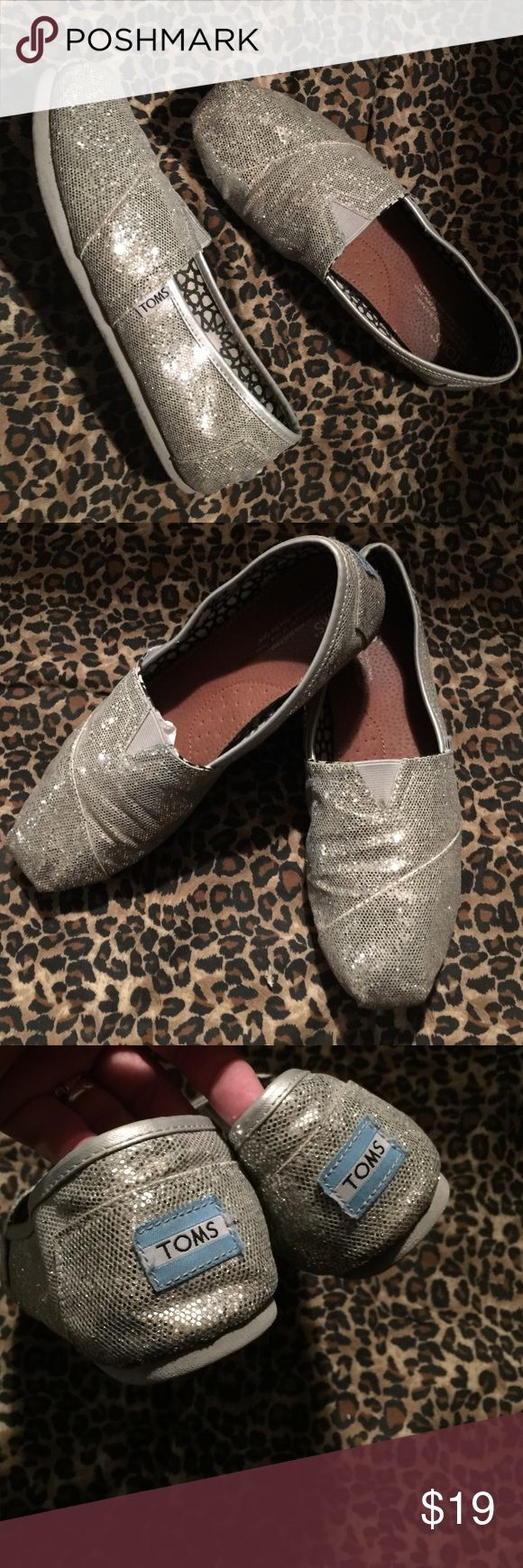 Shiny silver sparkle glitter TOMS canvas slip ons Lots of wear left in these! Worn just a handful of times! Great condition these are a women's size W9 (9-wide) pair of silver sparkly glitter Toms slip on canvas shoes!! Super comfy & super shiny pretty!! Stylish & perfect to throw on in the fall!! 🍁🍂🍁🍂 Any questions, please ask!! Thank you for looking & Happy Poshing 😊✌🏻️💕☀️🍁🍂😍 TOMS Shoes Flats & Loafers