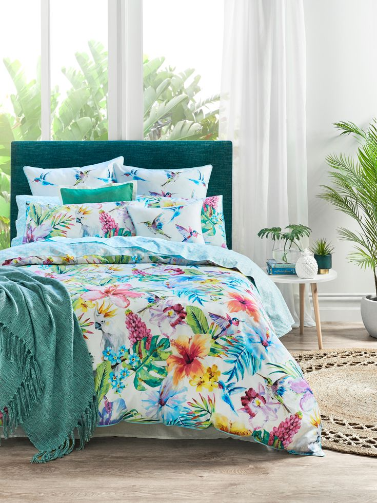 Vibrant cockatoos and colourful hummingbirds hide amongst large exotic flowers to create the tropical design of the Palm Cove quilt cover. Printed on luxurious 360 thread count cotton sateen, the quilt cover features bold, hand painted brush strokes to create a bright, textural effect. Featuring a sea blue flat piping trim and refreshing geometric reverse, create a complete look with the reversible European pillowcases and co-ordinating cushion. #bedroom #quiltcover #bedbathntable