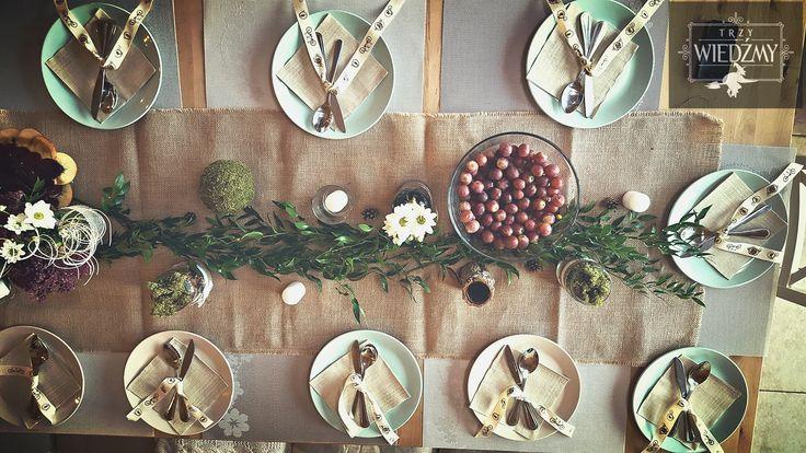 Rustykalne, naturalne, męskie, 60, urodziny. Widok stołu imprezowego z góry. Dekoracja w postaci zielonej girlandy z liści, biało - fioletowych bufetów w słoikach owiniętych ekologiczną wstążką, mech, szyszki. Dekoracja sztućców - wstążka z rowerami. /Rustic, fall, natural, wood, woodland, eco, birthday, man, party, 60, 60th decorations, ideas, leaves, gerland, table, ribbon, bike, white, green, brown, purple, flowers, centerpieces, mason jar, lace,place seat.