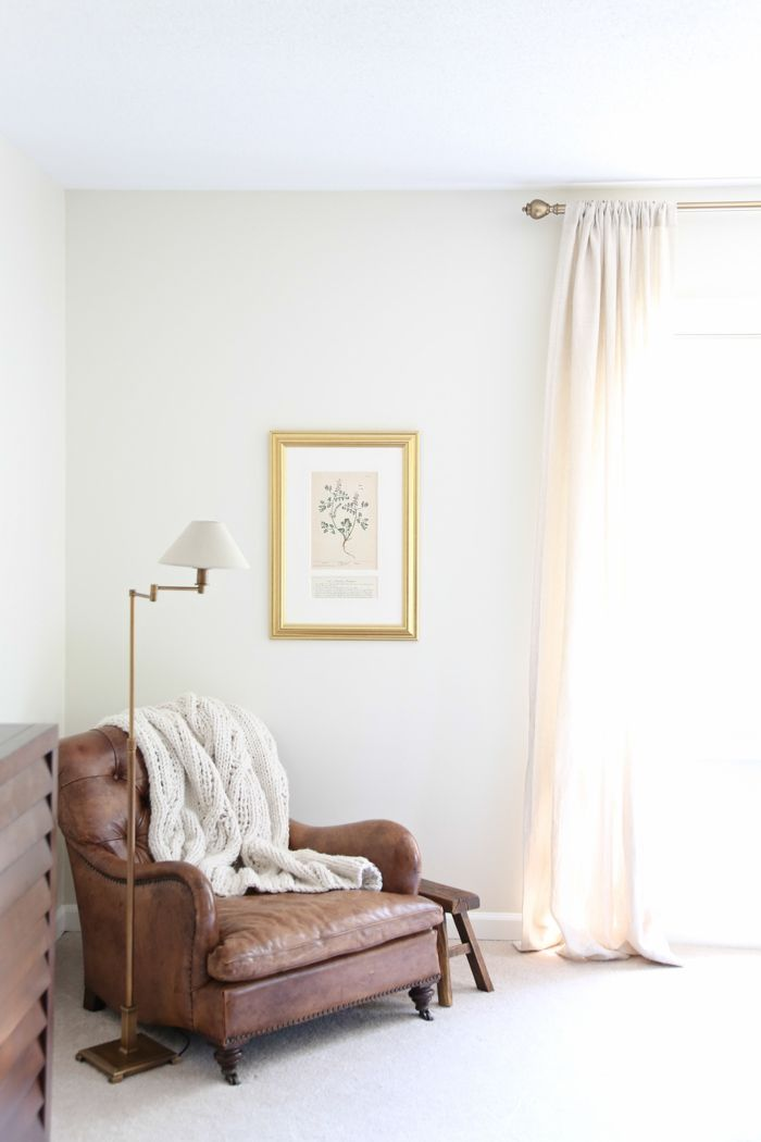 Feminine touch of a rolled arm on this masculine leather chair sitting in a Master bedroom reading nook