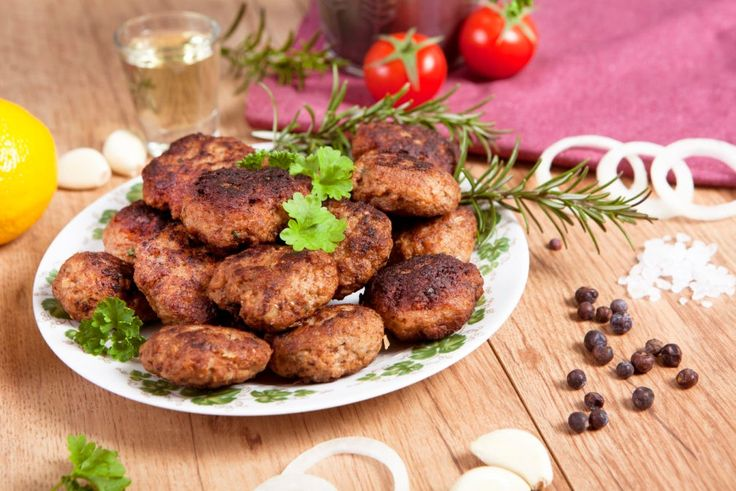 53293462 - homemade meatballs on a plate served with various ingredients on a wooden table