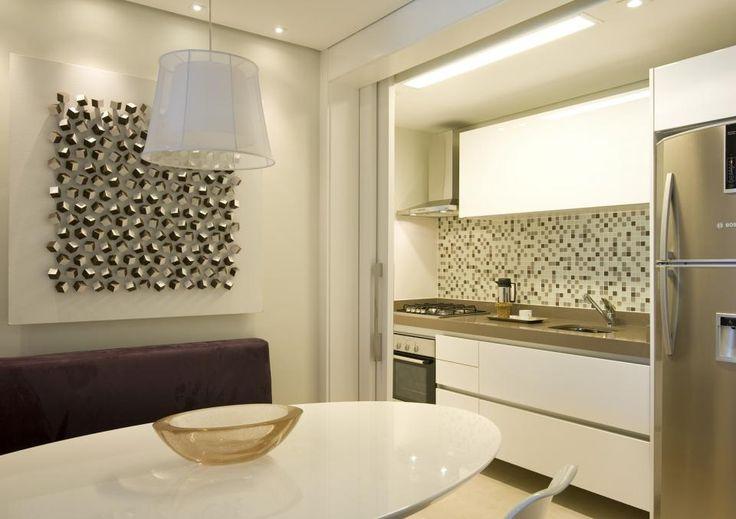 Cozinha integrada com sala de jantar. Detalhes de decoração tornam o ambiente sofisticado e acolhedor. Reforma e projeto de interiores em apartamento de 70m2, Moema, São Paulo.