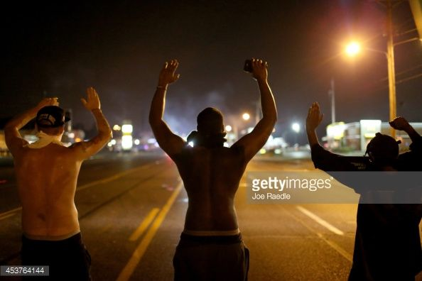 News Photo : Demonstrators raise their arms and chant, 'Hands...