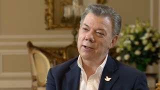 Image caption                                      El presidente de Colombia, Juan Manuel Santos, firmará este lunes el acuerdo de paz pactado entre el gobierno y los líderes de las FARC.                                Juan Manuel Santos se veía sereno, ya casi triunfal. De saco azul y camisa blanca sin corbata, con el prendedor de la paloma de la paz que siempre lleva en la solapa, el presidente de Colombia