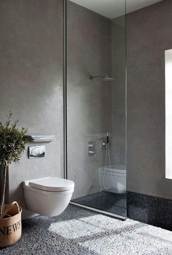 Baño actual con paredes de microcemento,  mampara de cristal y pavimento de cantos rodados