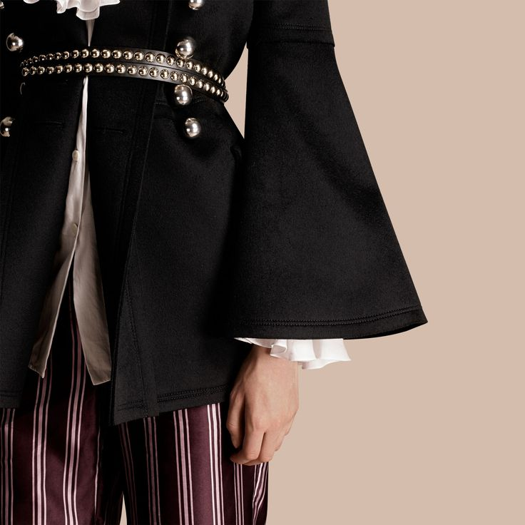 A structured black Burberry jacket cut from authentic military wool for noticeable warmth. The design is tailored to define the waist with a flared skirt and striking bell sleeves. Decorative domed buttons adorn the front.