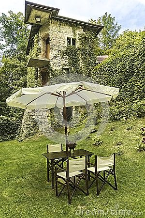 The table and chairs under the umbrella. Near the castle in Korzkiew , Poland