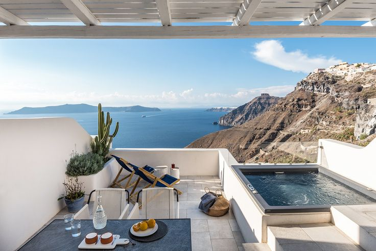 Beautiful roof terrace with jacuzzi and dining space overlooking the Santorini sea aboratorium renovate seven suites at Porto Fira luxury hotel in Santorini, Greece. Luxury hotel designs feature on the www.martynwhitedesigns.com interior design blog.