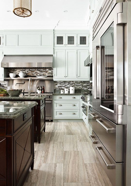 High-end kitchen remodel in a 1920s Georgian home by Designer/Architect Dee Dee Taylor Eustace. Pale blue cabinets, restaurant quality stainless appliances, double islands and sinks, quartzite countertops, and a honed limestone floor create a polished look.