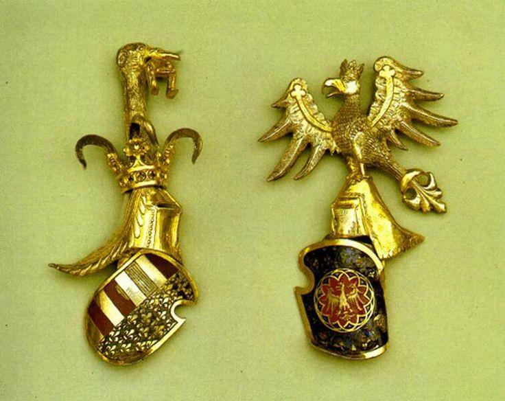 Címerpajzsok az aacheni kincsbõl - BAL:  Nagy Lajos sisakdísze az Aachen-ben őrzött palástcsaton (Nagy Lajos 1367-ben magyar kápolnát emeltetett Aachen-ben, a honi zarándokok számára.) Természetes volt tehát, hogy Nagy Lajos a magyar kápolna emeltetésekor fejedelmi ajándékokkal is emelte az alapítás fényét.  A fent látható palástcsat, alighanem budai ötvösök remekmívű munkája, mely a magyarországi Anjou-k ún. teljes címerét formázza, ekkor került más magyar kincsekkel együtt Aachen-be.