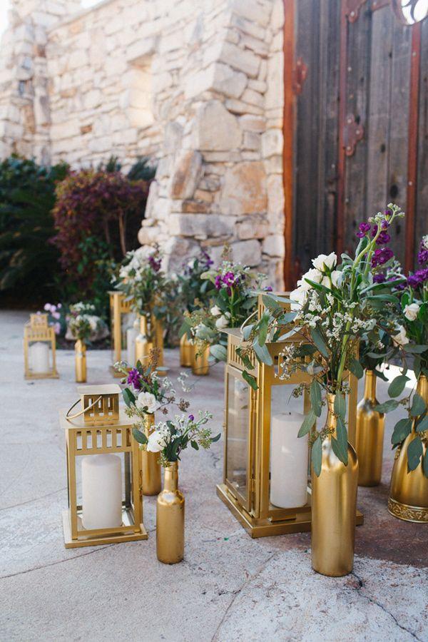 gold lanterns and spray-painted bottles, photo by Awake Photography http://ruffledblog.com/one-world-theatre-wedding #weddingideas #goldbottles #weddingdecor