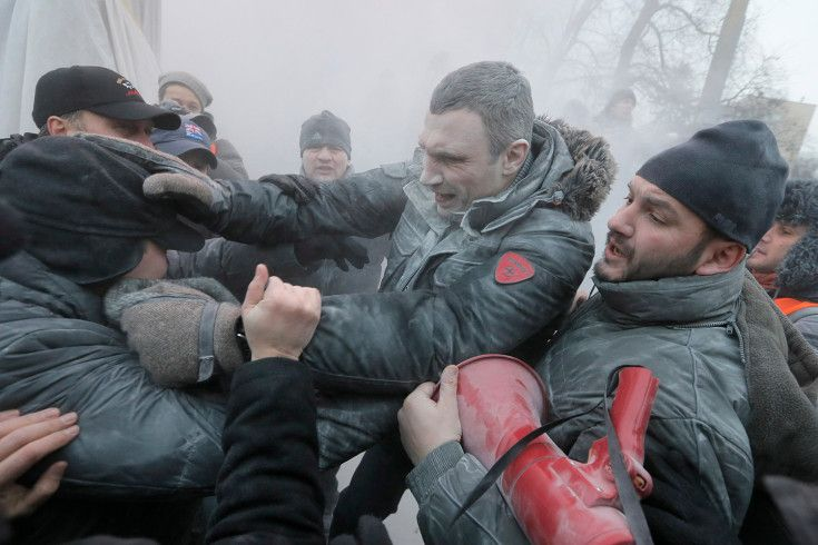 Opposition leader and former WBC heavyweight boxing champion Vitali Klitschko, center, is attacked and sprayed with a fire extinguisher as h...