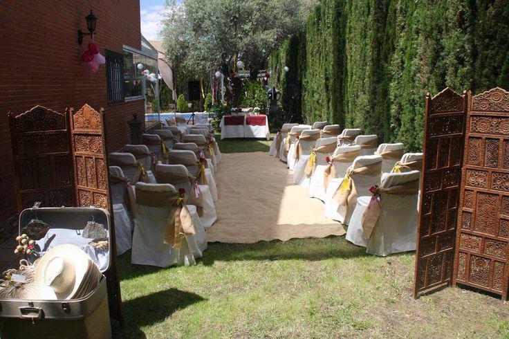 Sobre las fundas de las sillas , atamos una tira de rafia anudada en un lateral para añadirle unos lazos y unas florecillas y realzar así el pasillo de rafia que atravesamos hasta llegar a la mesa de ceremonia