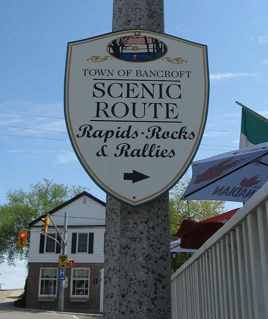 Road sign in downtown Bancroft, Ontario, tells you you're taking the scenic route.