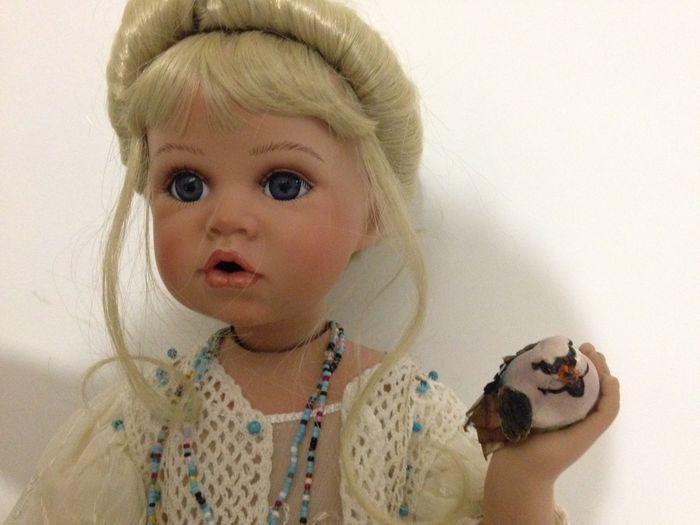 Porselein verzamelaars doll - nieuwstaat - jaren 1990  Duitse handgemaakte doll - porselein gezicht armen en benen. Doek lichaam. Deze kleine dame zit met haar benen buigen en houdt een vogeltje in haar handen. Ze heeft blond haar en haar kapsel is in perfecte staat. Altijd weergegeven in een glazen kast en nauwelijks behandeld.Deze pop kan alleen zitten en in zittende positie ze 27cm/11 inches hoog is. Haar volledige lengte dus met inbegrip van de lengte van haar benen ze is 55cm lang…