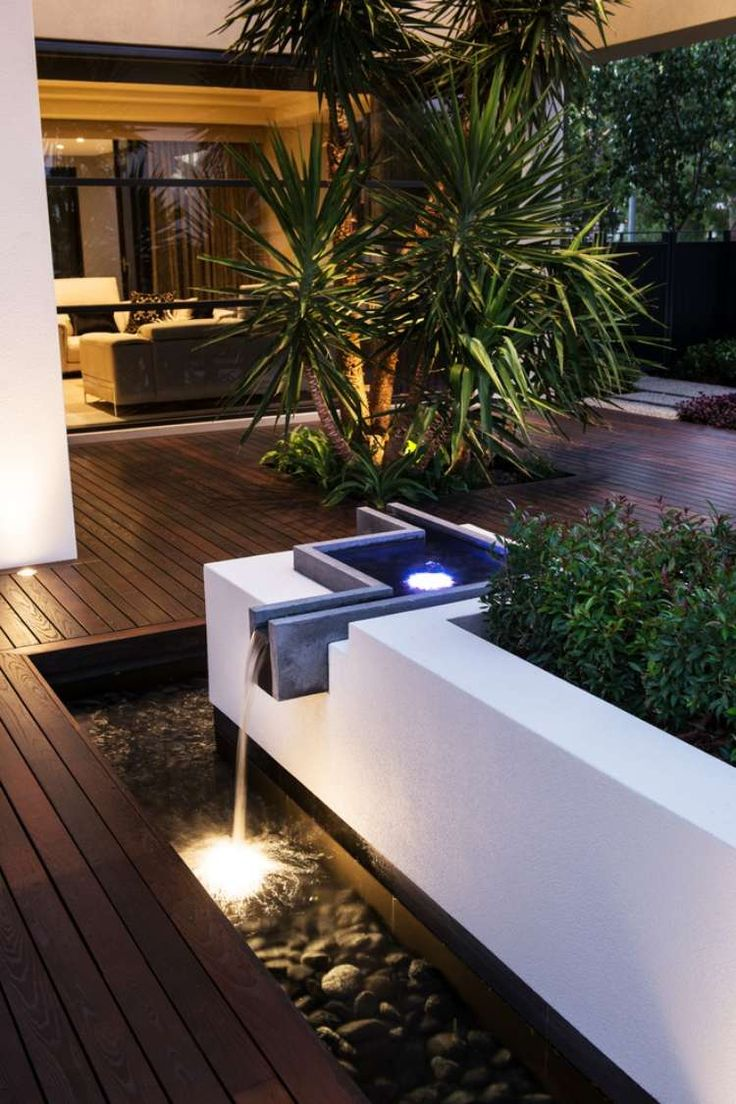 terrasse en bois composite avec des palmiers et fontaine en cascade