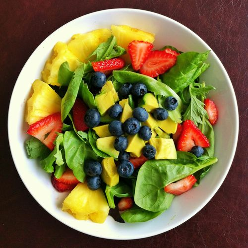 HEALTHY FOOD- Fruit salad featuring spinach blueberries pineapples strawberries and avocado