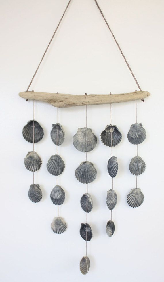 A simply beautiful handmade shell mobile. Authentic Scallop Sea Shells and driftwood collected from Texas Gulf of Mexico beaches are used to create this graceful mobile. I love to take long walks on the beach, its one of my favorite past times. On my past trip there was an abundance of these pretty grey toned scallops. Once home I cleaned and hand drilled the holes in the shells. Then I carefully knotted each one using a durable nylon cord. Each set of shells is suspended from the piece of…