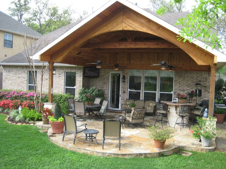 Custom designed and built gable roof addition with arch, outdoor kitchen, and flagstone patio.