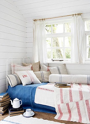 How to decorate a bed with red and blue detailed cushions made from vintage Hungarian linen