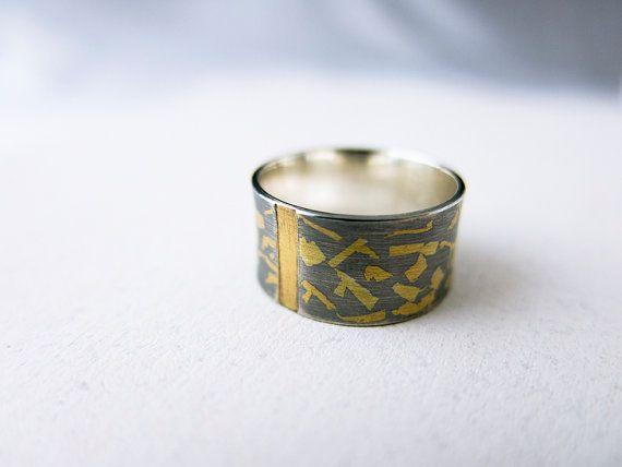 Anillo de plata de ley oxidada con trozos de lámina de oro de 24 quilates y con un canal hendido perpendicular al anillo también con lámina de oro, y con