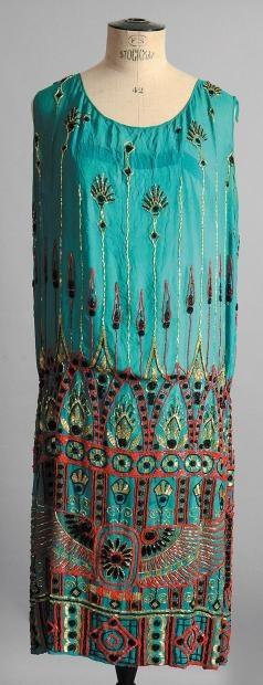 Robe du soir, vers 1923, tunique sans manches en mousseline de soie vert émeraude; décor brodé en perles de verre corail, dorées et noires rehaussé de cabochons et navettes de jais de frises géométriques, lotus et aigle inspirés de lantiquité égyptienne, fond de robe attenant, (petite tache, quelques manques). La découverte du tombeau de Toutankhamon et de son fabuleux trésor en 1922 fut un évènement marquant de l'époque et inspira les Arts appliqués.