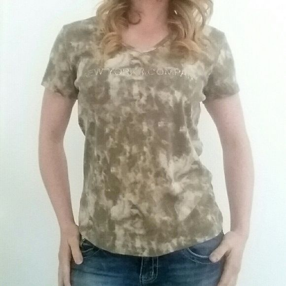 "NY&CO Beige Tee Camo/Tie-Dye This New York & Company top has a nice Camo/Tie-Dye look. Boasting hues of beige and olive. ""New York & Comapny"" is written in rinestone gems on the front of the tee. Great condition. 100% Cotton. XL New York & Company Tops Tees - Short Sleeve"