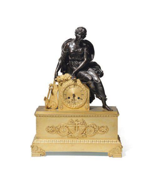 PENDULE en bronze patiné et doré à décor en ronde bosse d'une femme accoudée