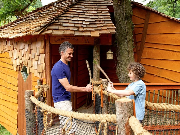 Father and son playing outside their treehouse cabin at Deerpark, Cornwall.