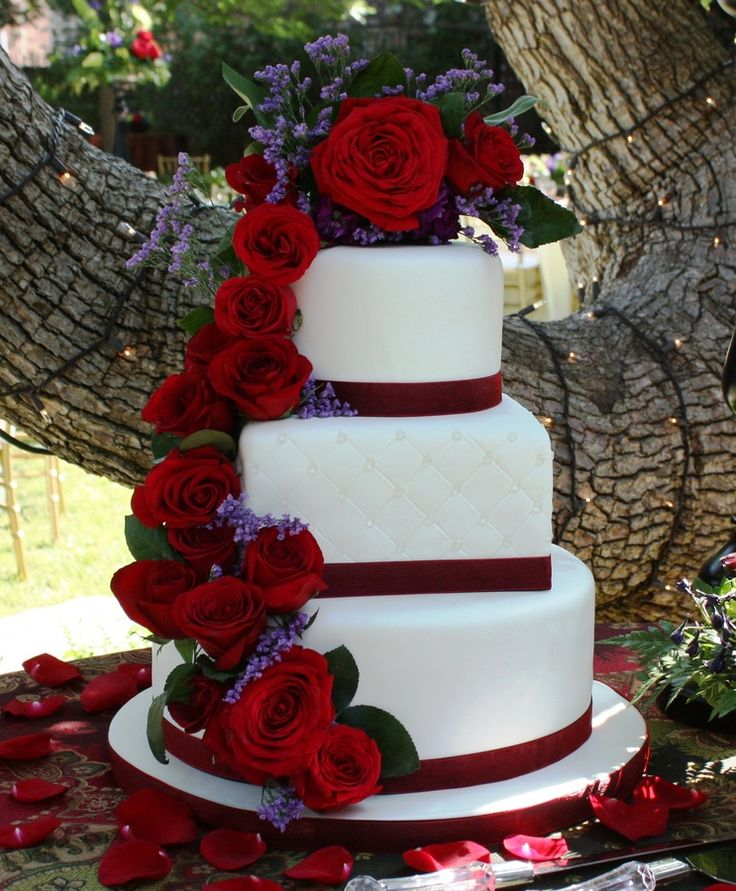 """12"""" round/8""""square/6"""" round fondant covered cake. Fresh roses cascading down. Square tier is quilted and decorated with edible diamonds or pearls."""