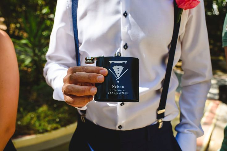Groomsmen in suspenders with personalised flask. Cake & Confetti Weddings. Photo by Quemcasaquerfotos
