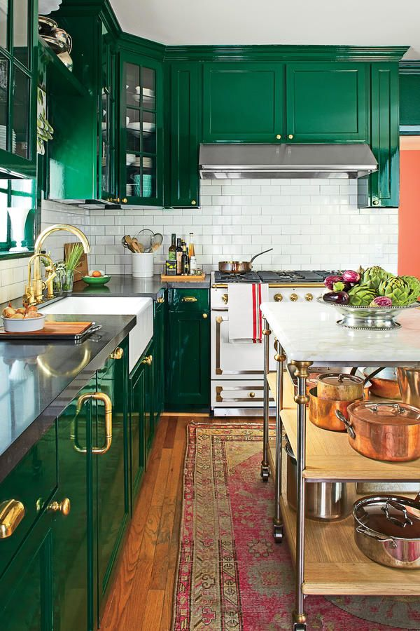 Bold Redo: After - Before-and-After Kitchen Makeovers - Southernliving. The homeowners replaced their lower cabinets and gave the uppers new life with glass doors and brass hardware. They drenched the space in a deep, dark green with a glossy, durable finish. A collection of white dishes, an impressive La Cornue range, and a white subway-tile backsplash bring neutral balance.