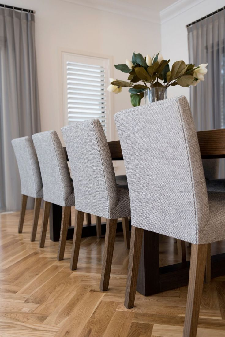 Custom upholstered dining chairs in silver grey.