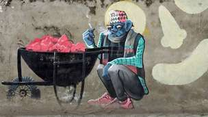 Mural shows a blue man enjoying a cigarette sitting by a wheelbarrow full of hearts