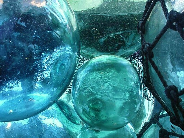 """Old Glass Floats-This is a stunningly beautiful antique glass fishing float found along the Alaskan coast. Made from recycled glass, usually saki bottles. There are no seams on this ball so I am assuming it was mouth blown without a mold. The trade mark on this float stands is the symbol for """"dai"""" which..."""